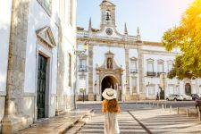 Young woman tourist standing on the city gate background in Faro town on the south of Portugal